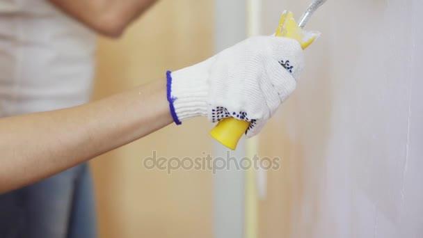 Detailansicht Der Womans Hand Im Handschuh Wandbemalung Mit Farbroller.  Fröhliches Junges Paar In Weißen Hemden