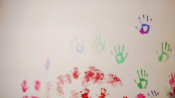 Šťastný matka a její roztomilý chlapec baví společně opouští své barevné otisky na zdi. Mladá rodina. Matka a dítě koncept