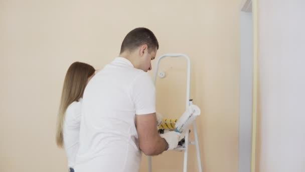 Junges Paar In Weißen Hemden Schmücken Ihre Neue Wohnung. Junger Mann Und  Frau Sind Die