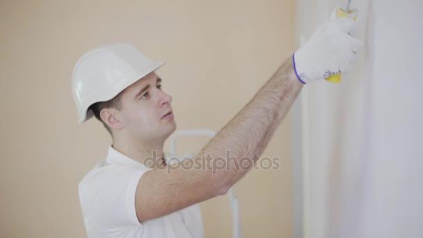junger Maler mit Helm bei der Arbeit beim Bemalen einer Wand mit einer Farbrolle.