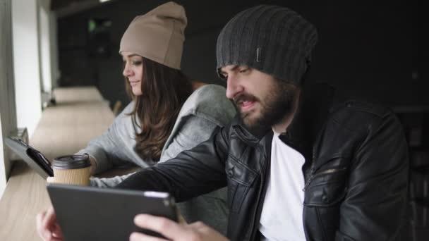 Pracovní schůzka v agentuře. Kreativní člověk a žena pomocí svých tabletů a diskutovat výsledky práce. Snímek v rozlišení 4k