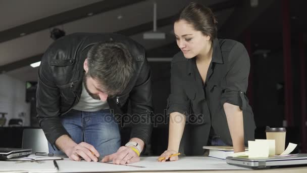 Mladý muž a žena pracující na projektu, kreslení a myšlení v moderní kanceláři. Používání kompasu. Šálek kávy a laptop na stole. Snímek v rozlišení 4k.