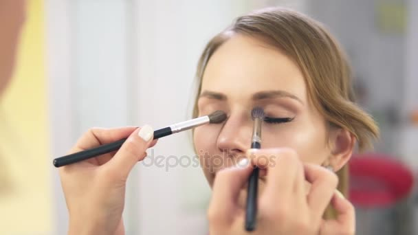 Closeup view of makeup artist applying eyeshadow on eyelid using makeup brush. Professional makeup. Slowmotion shot