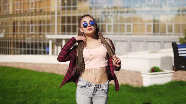 Krásná mladá dívka s dredy v parku. Krásná žena v džínách a sluneční brýle, poslouchá hudbu a tanec během slunečného dne. Slowmotion shot
