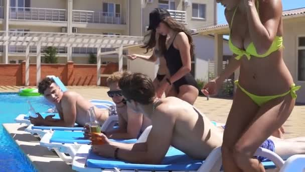 Men lying on coaches by the swimming pool, girls coming up and applying sun protection cream on their boyfriends back. Slowmotion shot.