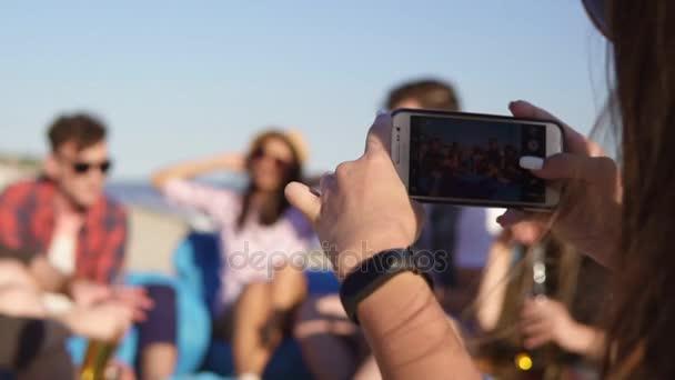 Detailní pohled dívky mladé bokovky, nahrávání videa nebo pořizování snímků s skupiny přátel, sedí na easychairs na pláži, hrál na kytaru a zpívá na letní večer. Slowmotion shot