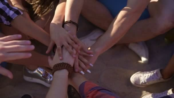 Closeup view of many hands united together and raised up. Teamwork and friendship concept. Group of friends sitting on easychairs on the beach on a summer evening. Slowmotion shot