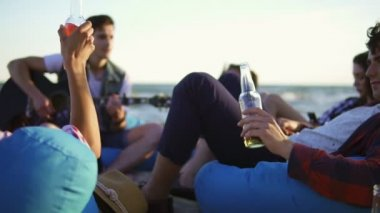 Group of friends drinking cocktails and beer and doing cheers sitting on easychairs on the beach and listening to a friend playing guitar on a summer evening during a sunset. Slowmotion shot