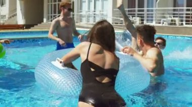 Young attractive people swimming on inflatable tubes on the pool party. Pretty women and men having a pool party. Shot in 4k