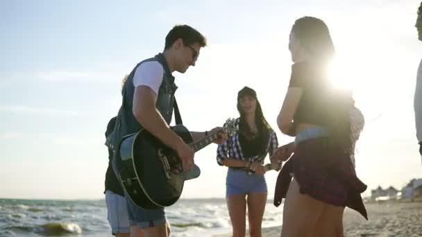Letní párty na pláži. Mladí přátelé pít koktejly, tanec v cirkle, hrál na kytaru, zpívá písně a potlesk na pláži na vodách hrany při západu slunce. Slowmotion shot