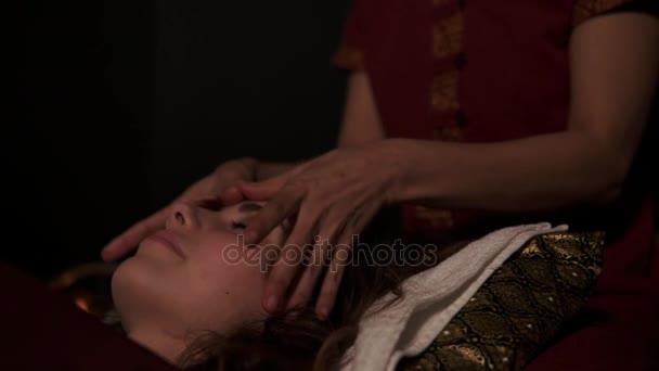 Masszázs terapeuta nem thai masszázs, nyak, fej és arc, nő, spa szobában a kanapén. Lassú mozgás, lövés
