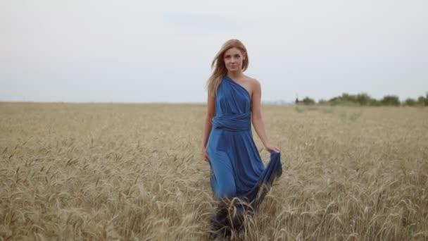 Szép, fiatal boldog lány hosszú kék ruhát keres, hogy a kamera aranyszínű Búzamező, séta. Szabadság fogalmát. Slowmotion lövés