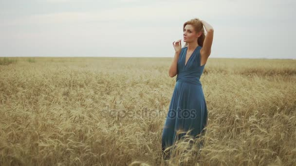 Handsome young woman in a long blue dress standing in golden wheat field trying the wheats stem, touching her hair and enjoying nature. Freedom concept. Slowmotion shot