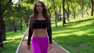 Usmívající se žena trenér v krátké sportovní top procházky v parku po  intenzivním tréninku. Zdravý 997da46bfd5