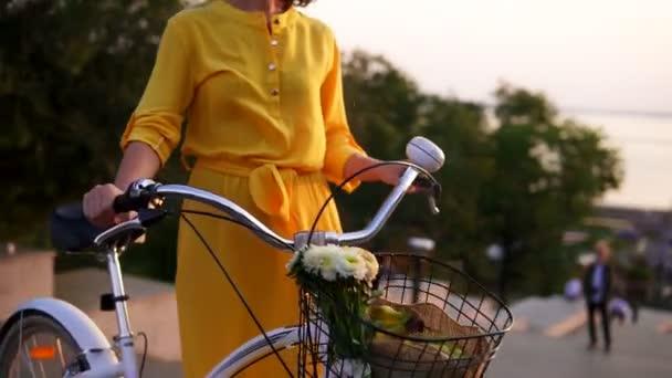 S úsměvem brunetka žena v dlouhých žlutých šatech stojící na její city kole drží jeho řídítka s květinami ve svém košíku během svítání brzy ráno. Odlesk objektivu, krásným výhledem na město