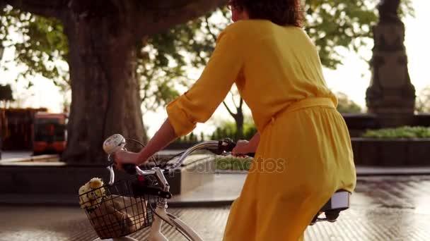 Zadní pohled nerozpoznatelné žena na koni citybike s košíkem a květiny v městském parku během svítání těší její čas brzy ráno. Odlesk objektivu. Slowmotion shot