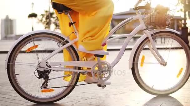 Detailní pohled na bílé město jízdní kola točí. Citybike zvonek, košík a květiny. Nelze rozpoznat žena, jízda na kole město brzy ráno. Steadicam zastřelen. Slowmotion