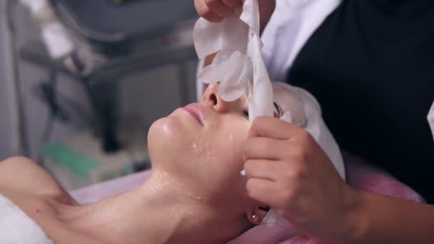 Cosmetologo femmina è una maschera speciale la rimozione dal fronte dei womans e pulizia viso con tamponi di cotone. Carbossiterapia professionale nel salone della stazione termale