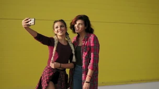 Dvě nejlepší friends holky pobaví a díky selfie stojící žlutá stěna. Dvě dívky bokovky fotografování selfie s chytrý telefon a usmívá se. Slowmotion shot