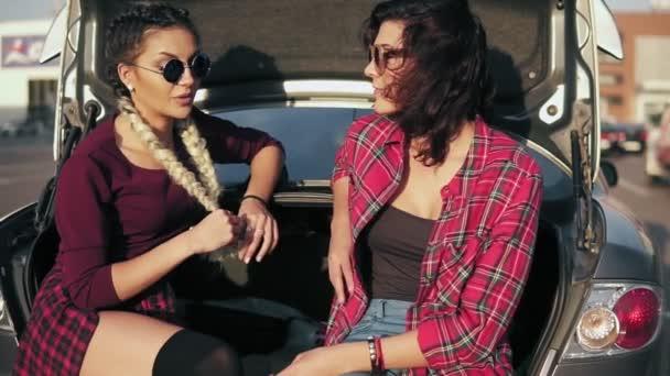 Dvě mladé atraktivní ženy ve stylové sluneční brýle sedí v kufru auta na parkovišti u nákupního centra a mluvení během slunného dne. Slowmotion shot