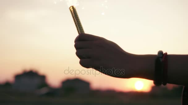 Two friends are lighting firework candles and celebrating together during sunset. Lens flare. Slowmotion shot