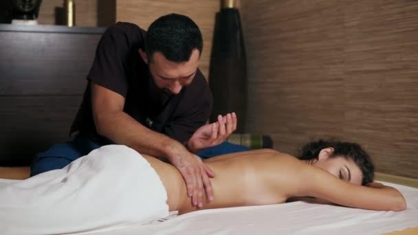Zkušený cokoliv v kimonu je masírování atraktivní dámy zpět. Krásná žena leží na podložce a přijímání thajské masáže ji zpět a ramena ve spa salonu. Slowmotion shot