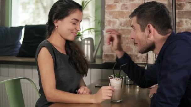 Atraktivní pár hraní a hloupé s mlékem protřepe v café uvedení šlehačkou na všech ostatních nos