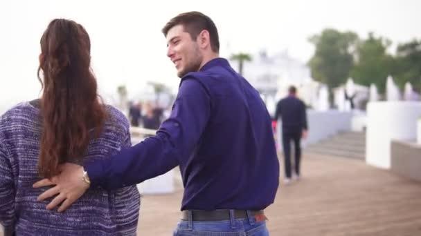 Nahaufnahme Rückenansicht eines jungen schönen Paares, das auf der Straße geht und sich umarmt. romantisches Date