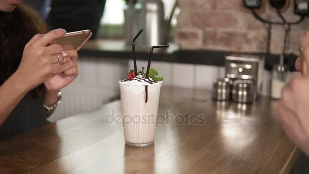 Kezét a férfi és a nő bevétel mozi-ból egy pohár tejet rázza a cseresznye a tetején és egy fából készült asztal kávézóban, használja a telefonját, szalma