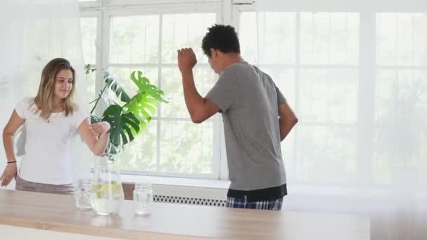 Slowmotion záběr šťastný mladý pár tančit, poslouchat hudbu v kuchyni na sobě pyžamo. Multikulturních pár v lásce baví doma