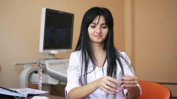 Mladá lékařka drží stříkačky připravuje, aby injekce v kanceláři lékaři. Snímek v rozlišení 4k