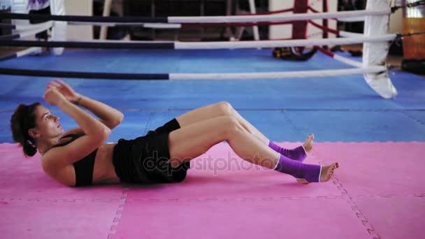 Sportovní mladá žena břišní sedů uvnitř ringu v tělocvičně. Boxerka trénink v tělocvičně. Snímek v rozlišení 4k