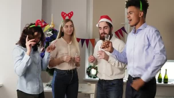 Multiracial group of happy office workers dancing during corporate New Year party wearing christmas hats and deer headband, holding glasses with sparkling wine and clinking