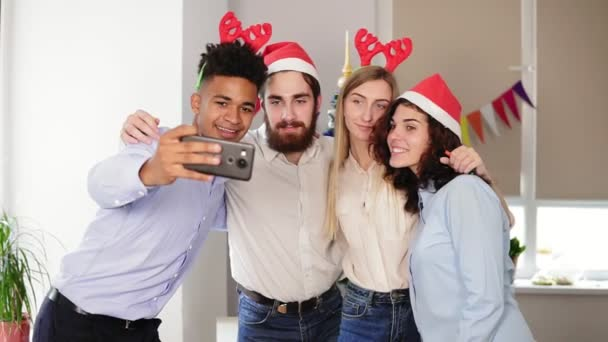 Happy business people in Santa hats are doing selfie and smiling while celebrating New Year in the office