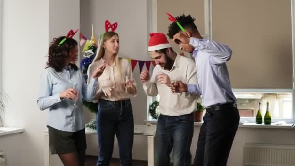 Slowmotion shot: Group of happy office workers dancing during corporate New Year party wearing christmas hats and deer headband, holding glasses with sparkling wine and clinking