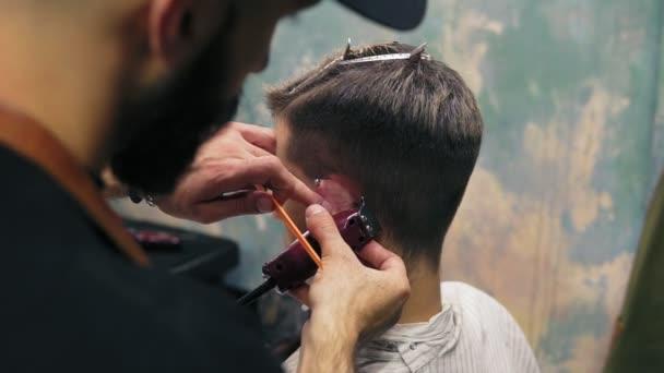 Vousatý holič vytvoření rovné čáry pomocí elektrický vyžínač za mans ucho. Mladý pohledný kavkazské muž u holiče v moderním kadeřnictví. Slowmotion shot