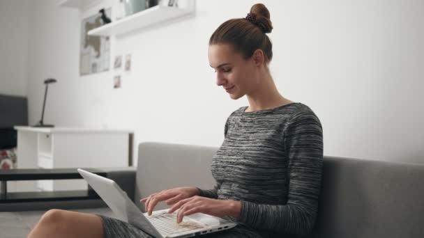 Mladá žena doma sedět na pohovce, je práce s přenosným počítačem a psaní textu na obrazovce