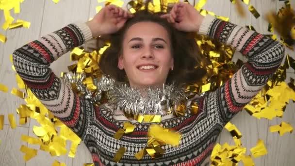 Boldog mosolygó lány feküdt a padlón, az arany konfetti esik neki. Után fél-idő. Vértes megtekintése. Lassú mozgás, lövés