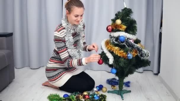 Příprava na Vánoce doma: mladá šťastná žena zdobí vánoční stromeček, závěsné hračky a usmívá se. Snímek v rozlišení 4k