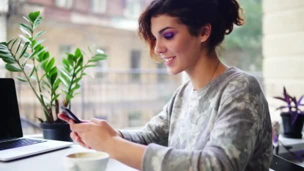 Detailansicht der schöne junge Frau mit ihrem Handy im Café und lächelnd. Frau mit app am Smartphone im Café trinken Kaffee und SMS auf Handy