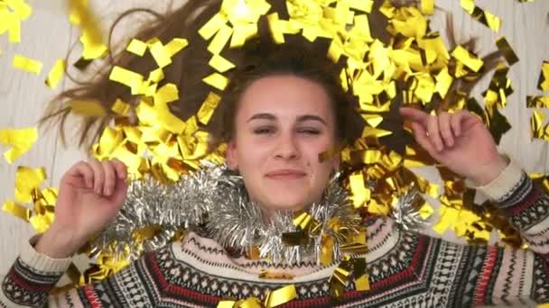Buli után: Vértes nézet fiatal boldog mosolygó nő feküdt a padlón, az arany konfetti esik neki. Lassú mozgás, lövés