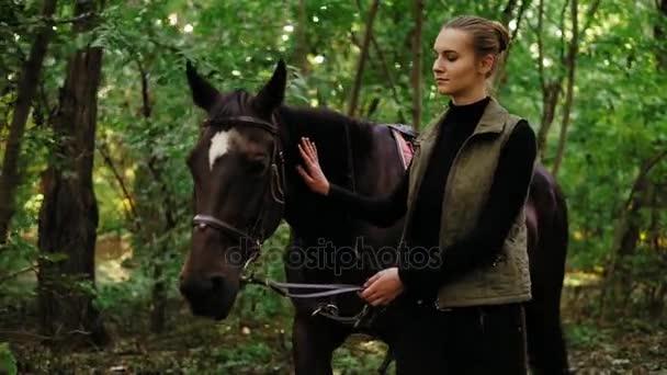 attraktive junge Frau Spaßvogel läuft mit braunem Pferd mit weißem Fleck auf der Stirn im Park an sonnigen Tagen mit Ledersattelband in der Hand