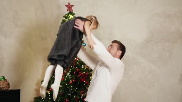 Christmas at home: young father playing with his daughter: he is throwing her in the air at home with decorated Christmas tree on the background
