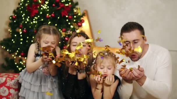 Young happy family of four sitting by the Christmas tree and blowing golden confetti. Cute mother, father and two daughters celebrating Christmas together. Slowmotion shot