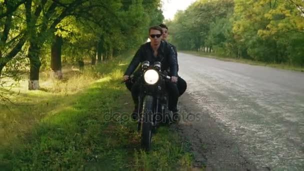 Pohledný muž v sluneční brýle s jeho přítelkyní, zastavení jeho vintage motocykl na straně silnice