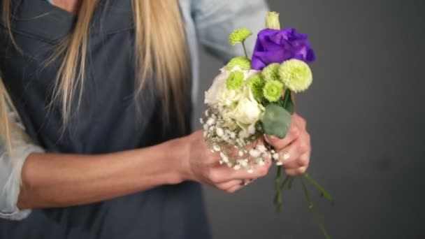 Slowmotion shot of hands of professional blonde female floral artist arranging beautiful bouquet at flower shop. Floristry, handmade and small business concept