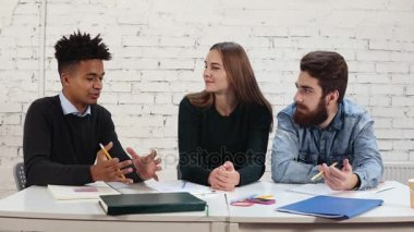 Young african guy explaining something to his collegues. Multiethnic group of people working together. Happy diverse group of students or young business team working on project. Slowmotion shot