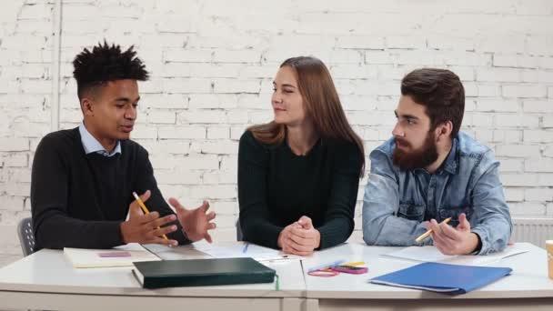 Mladí Afričan něco vysvětlovat jeho kolegové. Mnohonárodnostní skupiny lidí pracují společně. Happy různorodá skupina Studenti nebo mladí obchodní tým pracující na projektu. Slowmotion shot