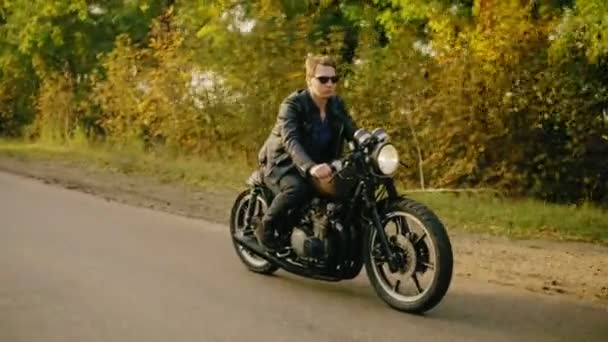 Elegantní muž v sluneční brýle a koženou bundu, jezdit na chladném kole na asfaltové silnici za slunného dne v lese na podzim. Krásné stromy s žluté listí kolem silnice