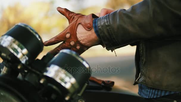 Side view of an unrecognizable motorcyclist taking brown leather gloves and wearing special leather mitts for riding in slow motion
